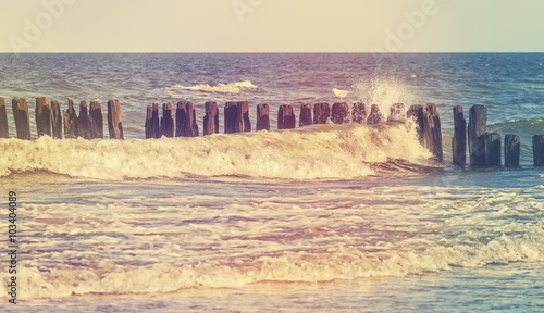 Retro stylized picture of wave crashing against wooden posts - 103404089