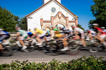 Cyclists  sports day, Orthodox Church in the background. Kihnu, small island in Estonia. Europe