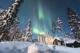 Beautiful picture of massive multicoloured vibrant Aurora Borealis, Aurora Polaris, also know as Northern Lights in the night sky over winter Lapland landscape