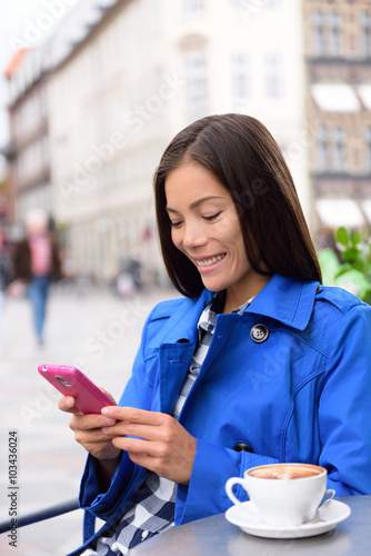 Asian business woman drinking coffee at oudoor terrace cafe texting or reading news on smart phone using app. European city center street of restaurants and cafes in fall autumn.