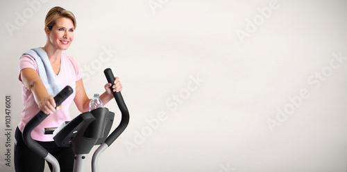 Mature woman doing exercise on elliptical trainer. © Kurhan