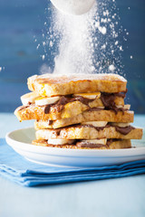 sprinkling powder sugar over french toasts with banana chocolate