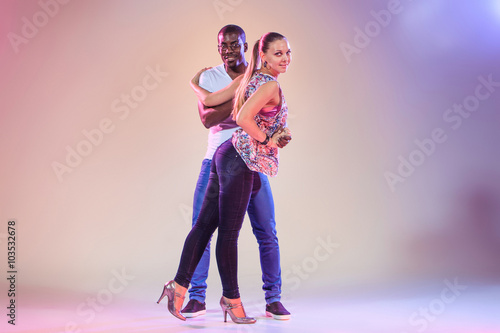 obraz lub plakat Young couple dances social Caribbean Salsa, studio shot