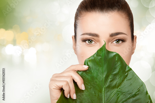 Gorgeous young woman with a fresh leaf to her face плакат