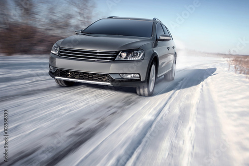 Gray modern car drive speed on road at winter daytime Poster