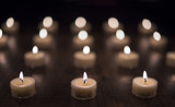 Lit Tea Light Candles on a Wooden Table (Front Focus)