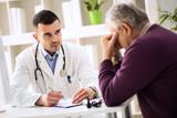 mladý lékař pozorně naslouchat pacient o svých bolestech