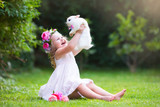 Little girl playing with real rabbit