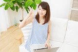 女性 リビング ノートパソコン OKサイン