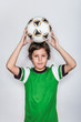 Cute Smiling Kid in Green Soccer Shirt Holding Soccer Ball Above Head