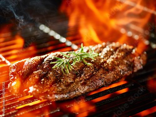 Fototapeta flat iron steak cooking on flaming grill with rosemary garnish