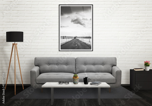 Road picture in vertical art frame on wall. Sofa, lamp, plant, glasses, book, coffee on table in living room interior.  © Stanisic Vladimir