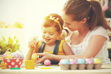 Fototapety happy family mother and child girl paints eggs for Easter