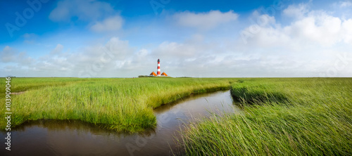 Foto op Canvas Noordzee Traditional lighthouse at North Sea with blue sky and clouds