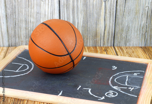 Fotobehang Basketbal An orange basketball and a play diagram good for March madness, championship or basketball season on wooden background