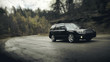 Black car fast drive on asphalt road at daytime