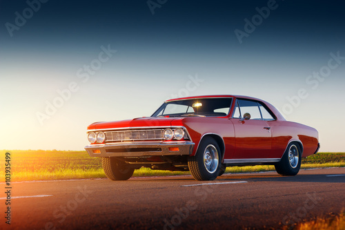 Retro red car stay on asphalt road at sunset Poster