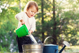 Fototapety Happy toddler girl playing with watering cans