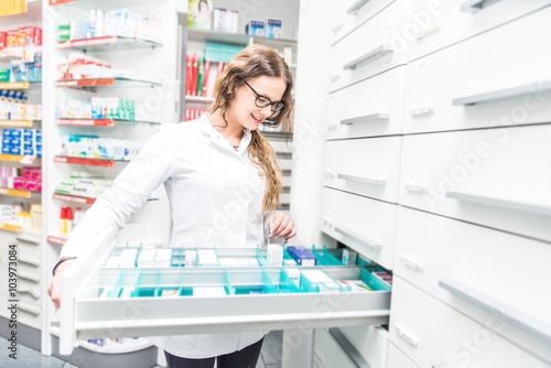 Papiers peints Pharmacie Female pharmacist taking a medicine from a shelf - Doctor opening a drawer in her pharmacy