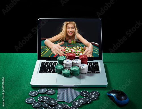 Green table with casino chips and cards on notebook плакат