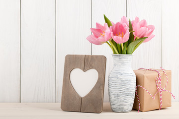 Fresh pink tulips, blank frame and gift box