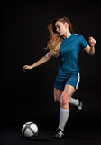 young woman football player kicking ball isolated on black background