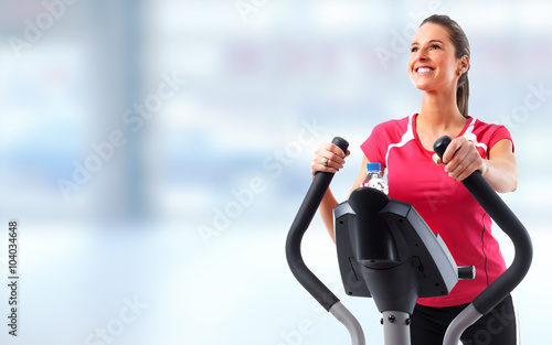 Young woman exercising on elliptical trainer. © Kurhan