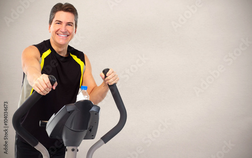Man exercising on elliptical trainer. © Kurhan