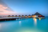 Water villas on Maldives resort island in sunset - 104056643