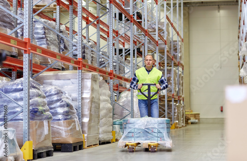 Poster Industrial geb. man carrying loader with goods at warehouse