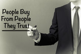 Business man writing - People Buy From People They Trust