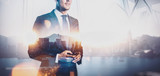 Fototapety Photo of  businessman holding smartphone. Double exposure, city on the background. Wide