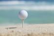 Golf ball on tee in sand beach with ocean waves behind