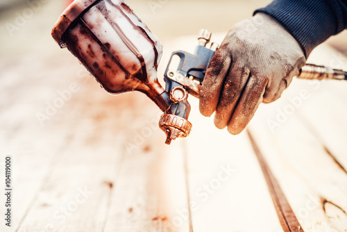 Poster Close up of a spray paint gun and worker hand
