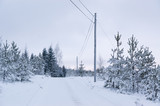 Winter landscape with small snowy country road in forest, Finland.