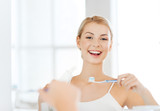 Fototapety woman with toothbrush cleaning teeth at bathroom