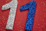 Number eleven silver blue color over a red background. Anniversa