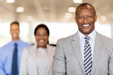 african businessman standing in front of colleagues