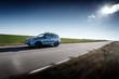 Blue car fast drive on asphalt road at daytime
