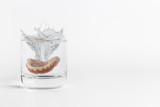 Dentures splashing in glass of water - 104330867