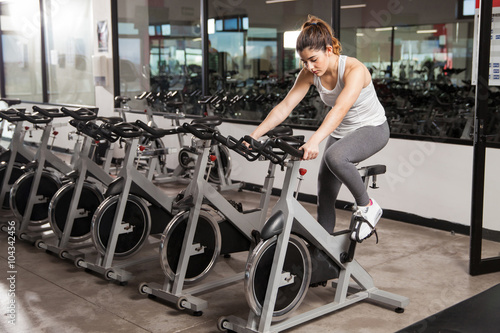 Beautiful girl doing spinning at the gym