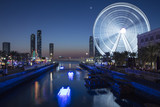 water channel with reflection and night light of ferris wheel in emirates city