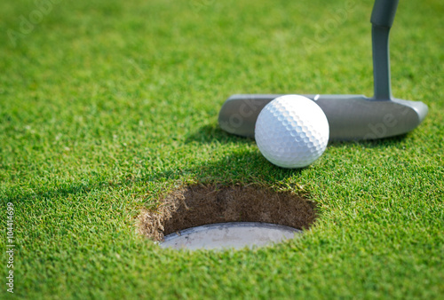 Fototapeta Close-up of golf hole with putter and ball