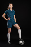 woman with foot on soccer ball in studio on black background