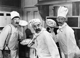 Three chefs holding pies for a fight in the kitchen  - 104427604