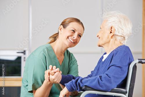Leinwanddruck Bild Krankenschwester hält Hand einer Seniorin