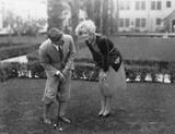 Man talking to woman while golfing  - 104435044