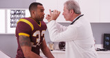 College football player having senior doctor review his concussi