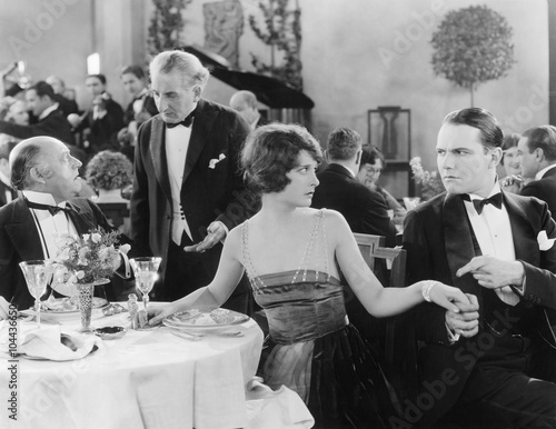 Young woman holding a man's hand at a different table while her companion is talking to the waiter  - 104436650
