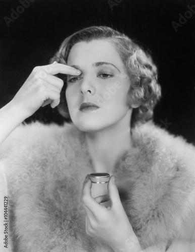 Portrait of woman applying makeup  - 104441229